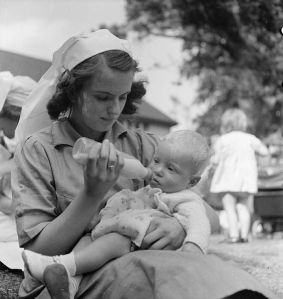 Baby being bottle-fed at a working mothers' Nursery, Birmingham, UK, 1942, from Wikimedia, PD-old
